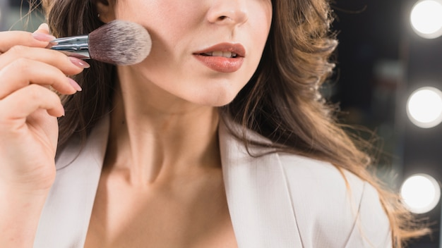 Bella donna che applica la polvere dalla spazzola di trucco