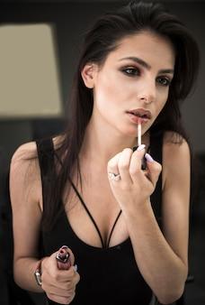 Bella donna che applica lucidalabbra
