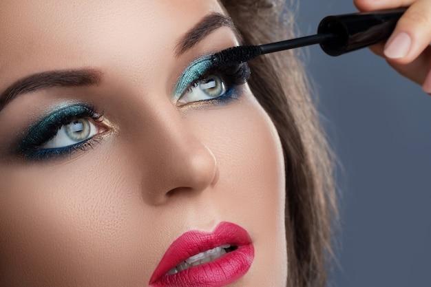 Bella donna che applica mascara sulle sue ciglia