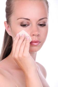 Bella donna che applica polvere sul suo viso