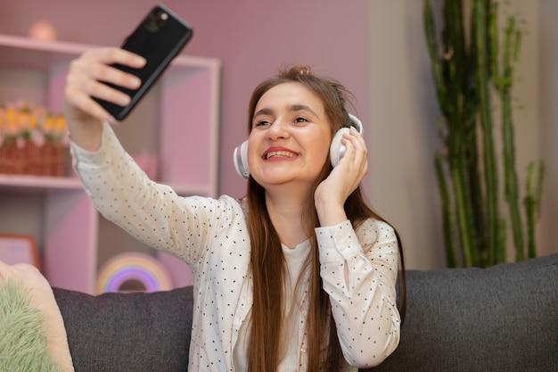Bella donna che ascolta la musica a casa. ragazza sorridente graziosa che prende selfie sullo smartphone, ascoltando la musica, sedendosi sullo strato a casa.