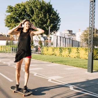 Bella donna che ascolta la musica mentre skateboarding sulla via