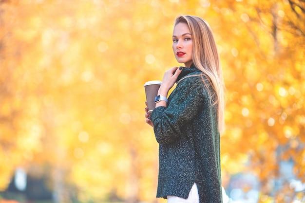 Bella donna che beve caffè nella sosta di autunno sotto il fogliame di caduta