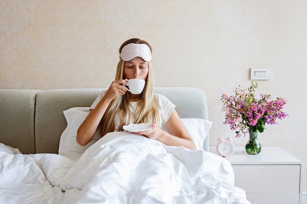Bella donna che beve il caffè a letto