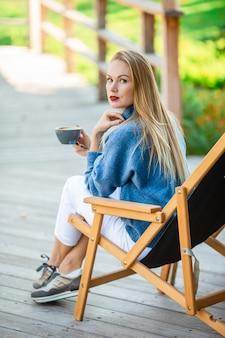 Bella donna che beve il caffè in autunno parco sotto il fogliame di autunno
