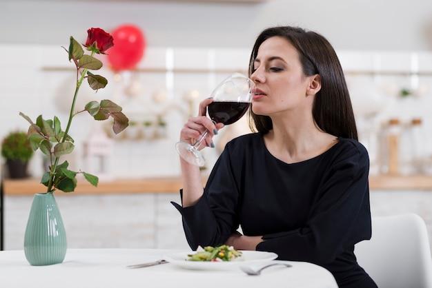 Bella donna che beve un bicchiere di vino rosso