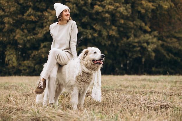 Bella donna che cammina fuori il suo cane in un campo