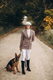 Bella donna che cammina fuori il suo cane nel parco di autunno