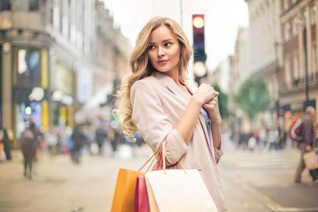 Bella donna che cammina per strada, tenendo le borse della spesa