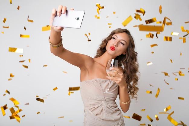 Bella donna che celebra il nuovo anno bevendo champagne