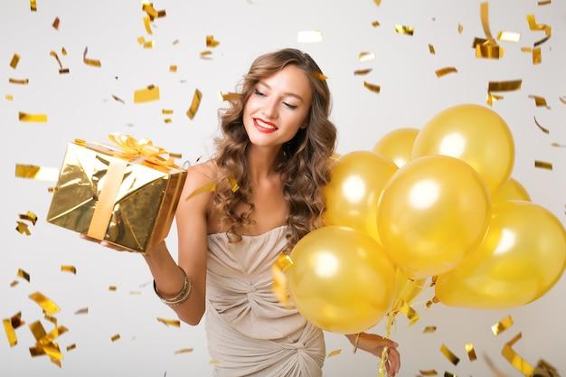 Bella donna che celebra il nuovo anno che tiene palloncini