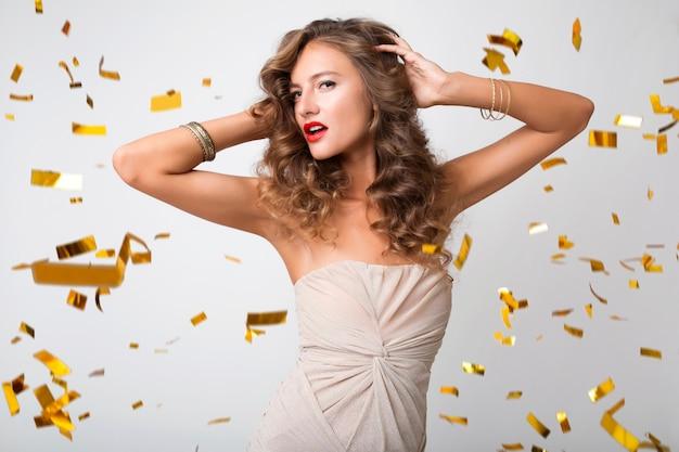 Bella donna che celebra il nuovo anno in coriandoli dorati