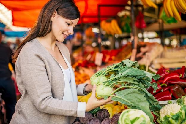 Bella donna che compra cavolo rapa al mercato.