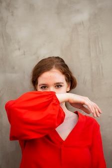 Bella donna che copre il viso con il braccio