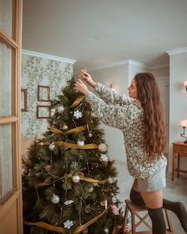 Bella donna che decora l'albero di natale nel salotto