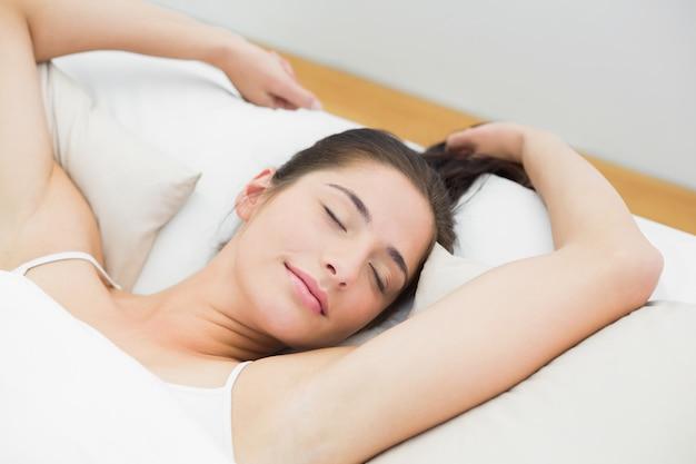 Bella donna che dorme nel letto con gli occhi chiusi