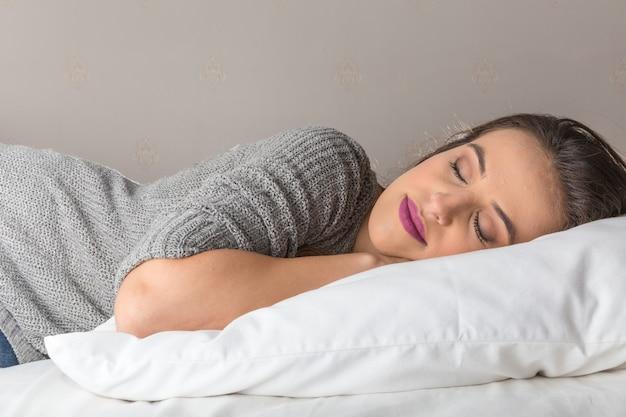 Bella donna che dorme sul comodo cuscino nel letto di casa