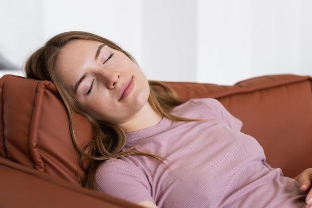 Bella donna che dorme sul divano