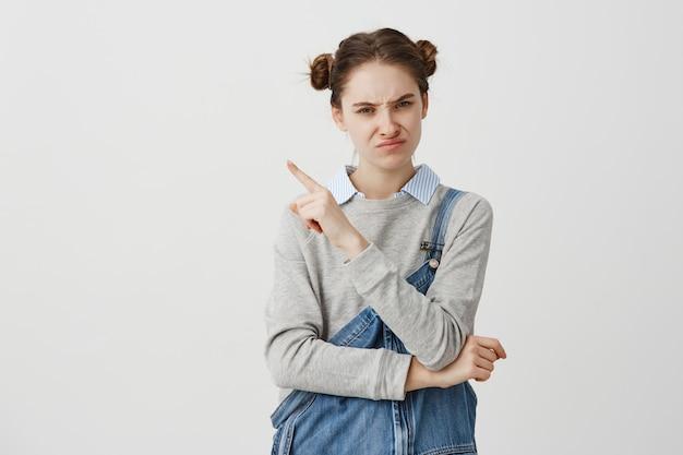 Bella donna che esprime insoddisfazione con il dito puntato a lato su qualcosa di spiacevole. la lavoratrice pubblica che è turbata di nuovo programma che gesturing su questo significato trascura. copia spazio