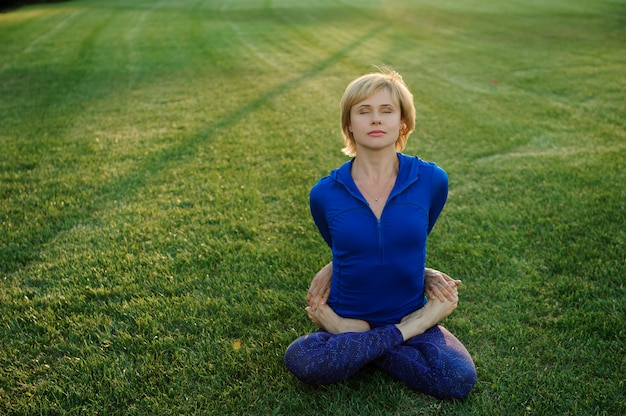 Bella donna che fa esercizi di yoga nel parco