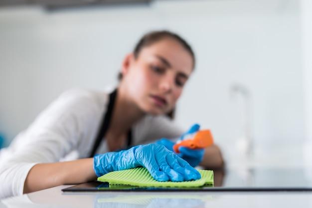 Bella donna che fa i lavori domestici mentre pulisce nella cucina