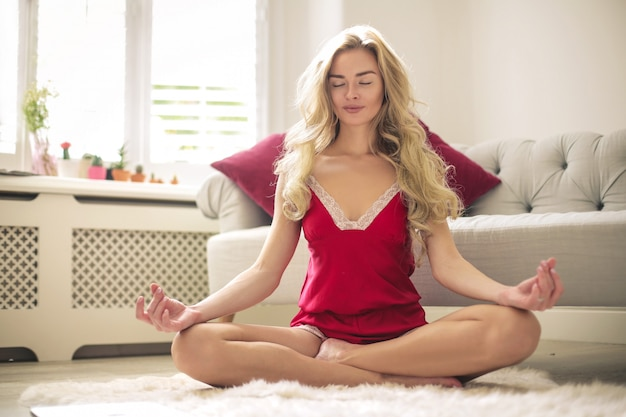 Bella donna che fa yoga a casa, nel suo salotto