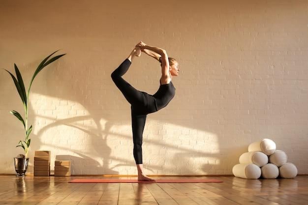 Bella donna che fa yoga al momento del tramonto in uno studio