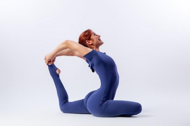Bella donna che fa yoga, in piedi in una posa equilibrante asana