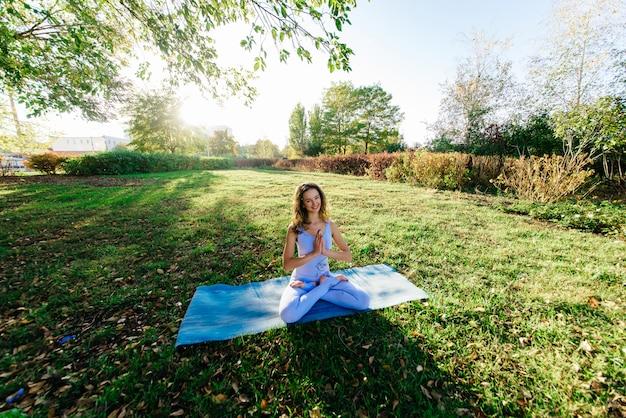 Bella donna che fa yoga su una scogliera, dietro un fantastico tramonto nel mare