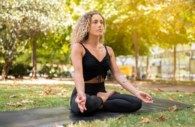 Bella donna che fa yoga sulla strada