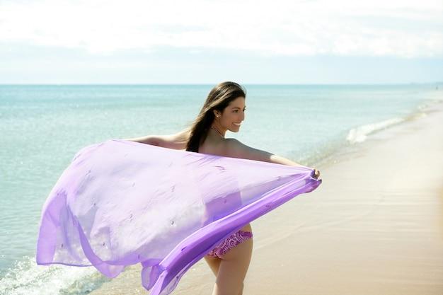 Bella donna che funziona in bikini sulla spiaggia