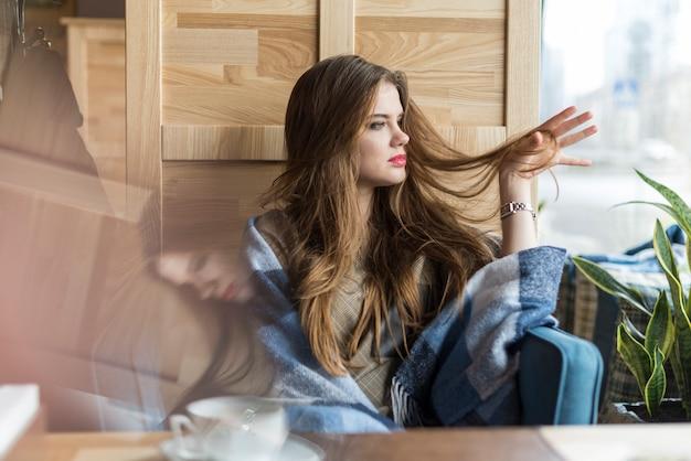 Bella donna che gioca con i suoi capelli, mentre guardando attraverso la finestra