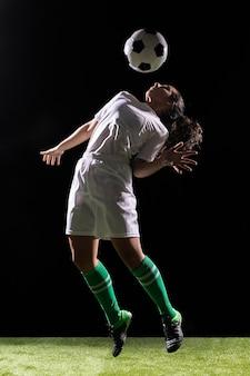 Bella donna che gioca con il pallone da calcio