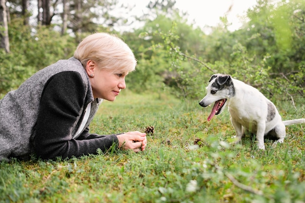 Bella donna che gioca con il suo cane nel parco