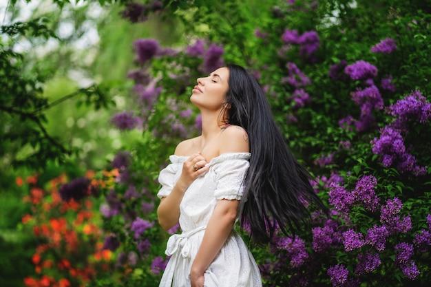 Bella donna che gode dell'odore del lillà. modello carino e fiori. concetto di aromaterapia e primavera