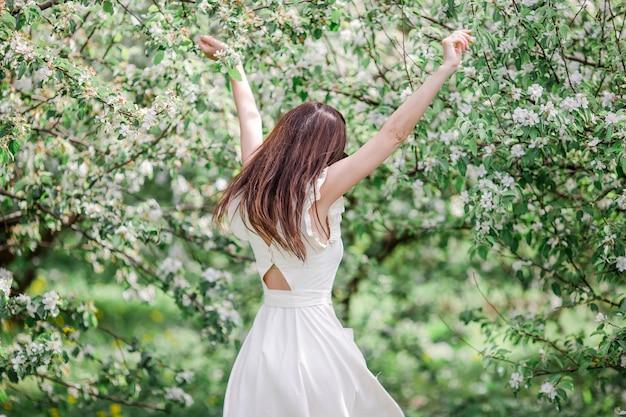 Bella donna che gode dell'odore nel giardino della ciliegia di primavera