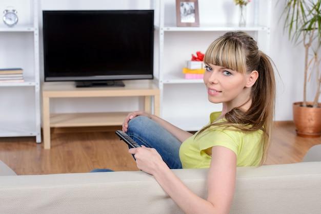 Bella donna che guarda tv seduto sul divano di casa