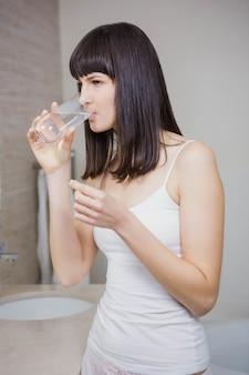 Bella donna che ha bicchiere d'acqua con medicina nel bagno