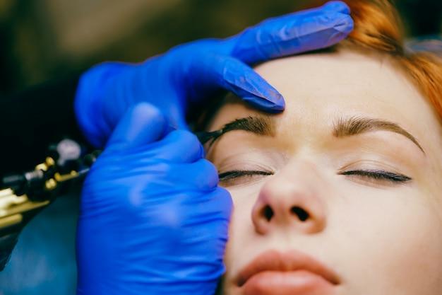 Bella donna che ha tatuaggio sopracciglio professionale nel salone di bellezza. procedura di trucco permanente sulle sopracciglia. primo piano, messa a fuoco selettiva.