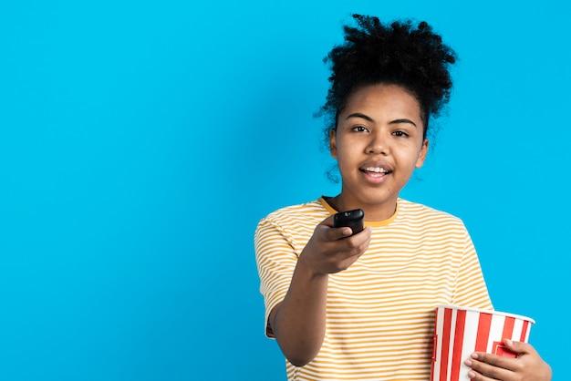 Bella donna che indica telecomando con il secchio del popcorn