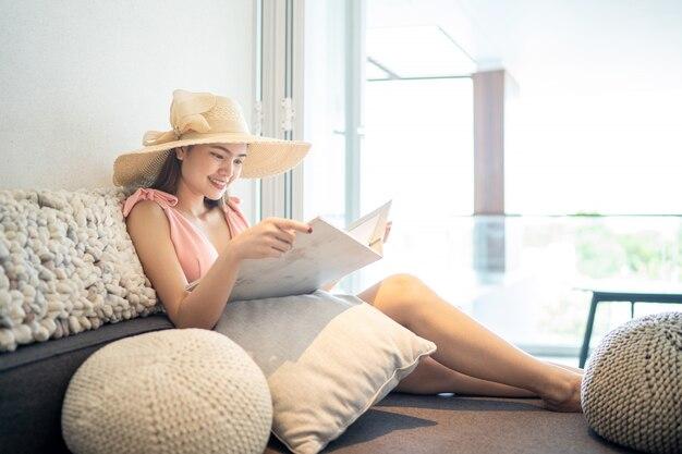 Bella donna che indossa bikini rosa siediti e leggi un libro su un comodo sedile nella stanza.