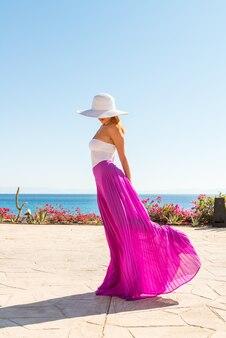 Bella donna che indossa cappello e gonna rosa