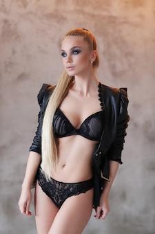 Bella donna che indossa giacca di pelle nera e sexy lingerie nera