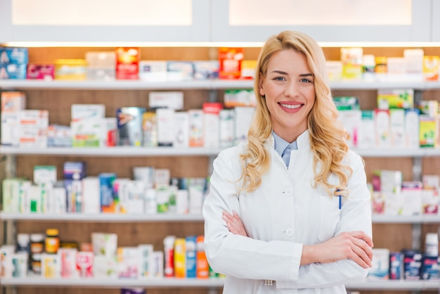 Bella donna che indossa in camice bianco che lavora in farmacia.