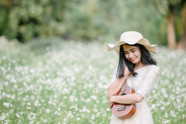 Bella donna che indossa un abito bianco carino e in possesso di un ukulele