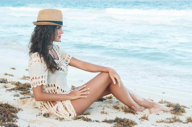 Bella donna che indossa un cappello sulla spiaggia