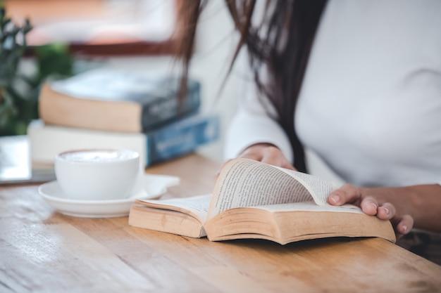 Bella donna che indossa una maglietta bianca che legge un tavolo di legno in una stanza bianca