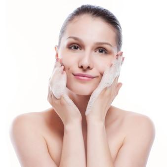 Bella donna che lava il suo fronte - isolato su bianco