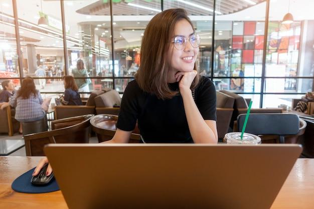 Bella donna che lavora con il computer portatile del computer in caffetteria