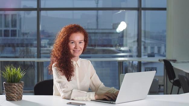Bella donna che lavora utilizzando il computer portatile che osserva in schermo monitor